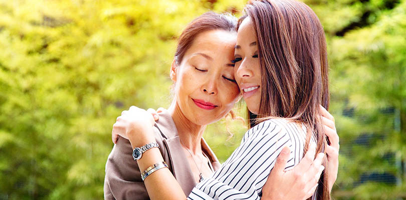 A mom and daughter are embracing each other