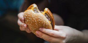 Person holding bitten burger