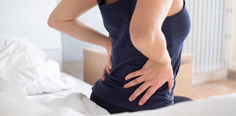 Woman sitting on edge of bed holding her lower back