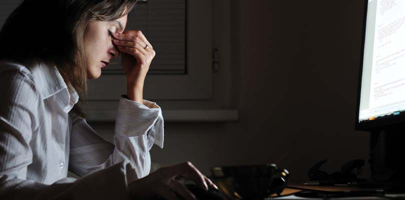 A woman sitting in front of a computer screen pinching her forehead in pain.