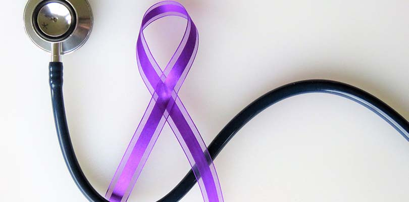 A purple fibromyalgia ribbon with a stethoscope against a white background.